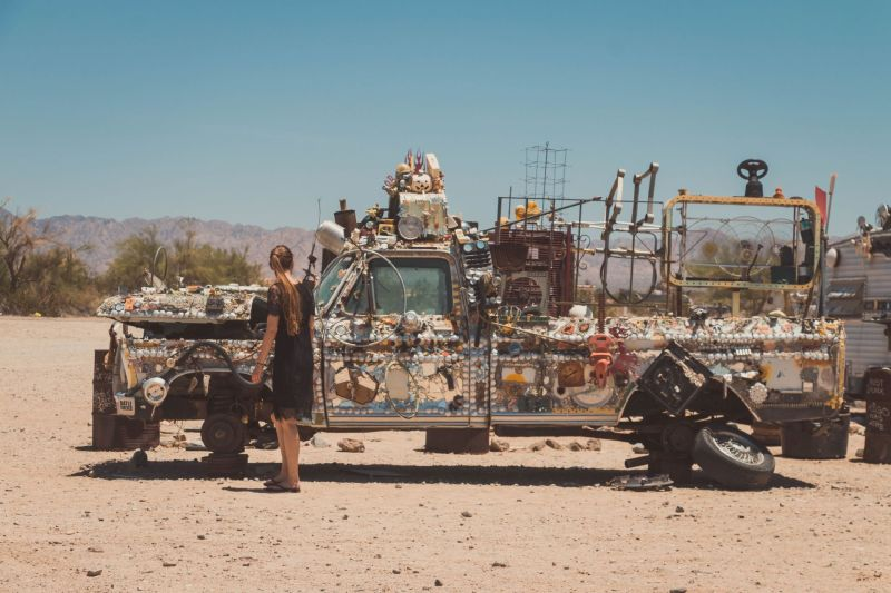 Junge Frau vor einem Kunst-Auto in Slab City