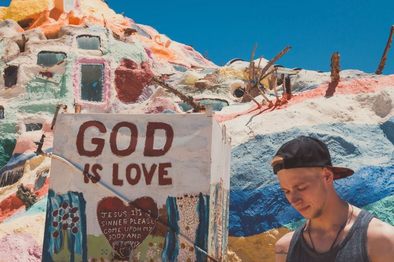 Junger Mann vor dem Salvation Mountain in Slab City
