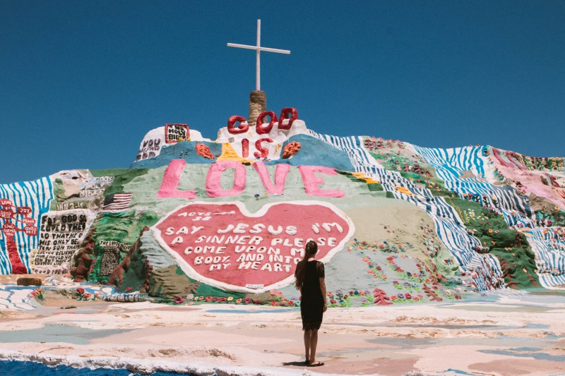 Junge Frau steht vor dem Salvation Mountain in Slab City
