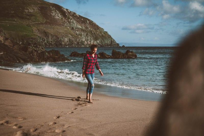 Frau am Strand an der Küste in Irland