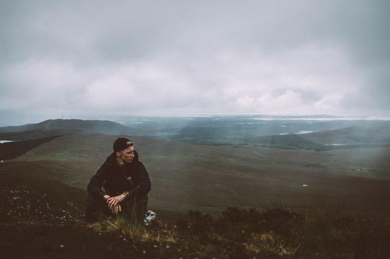 Junge auf einem Berg in Irland bei schlechtem Wetter